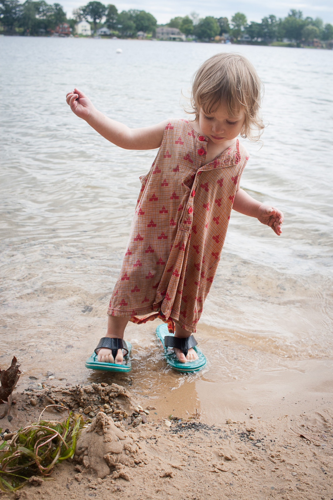 A girl on the edge of a beach, facing the camera, wearing flip flop shoes which are too large for her