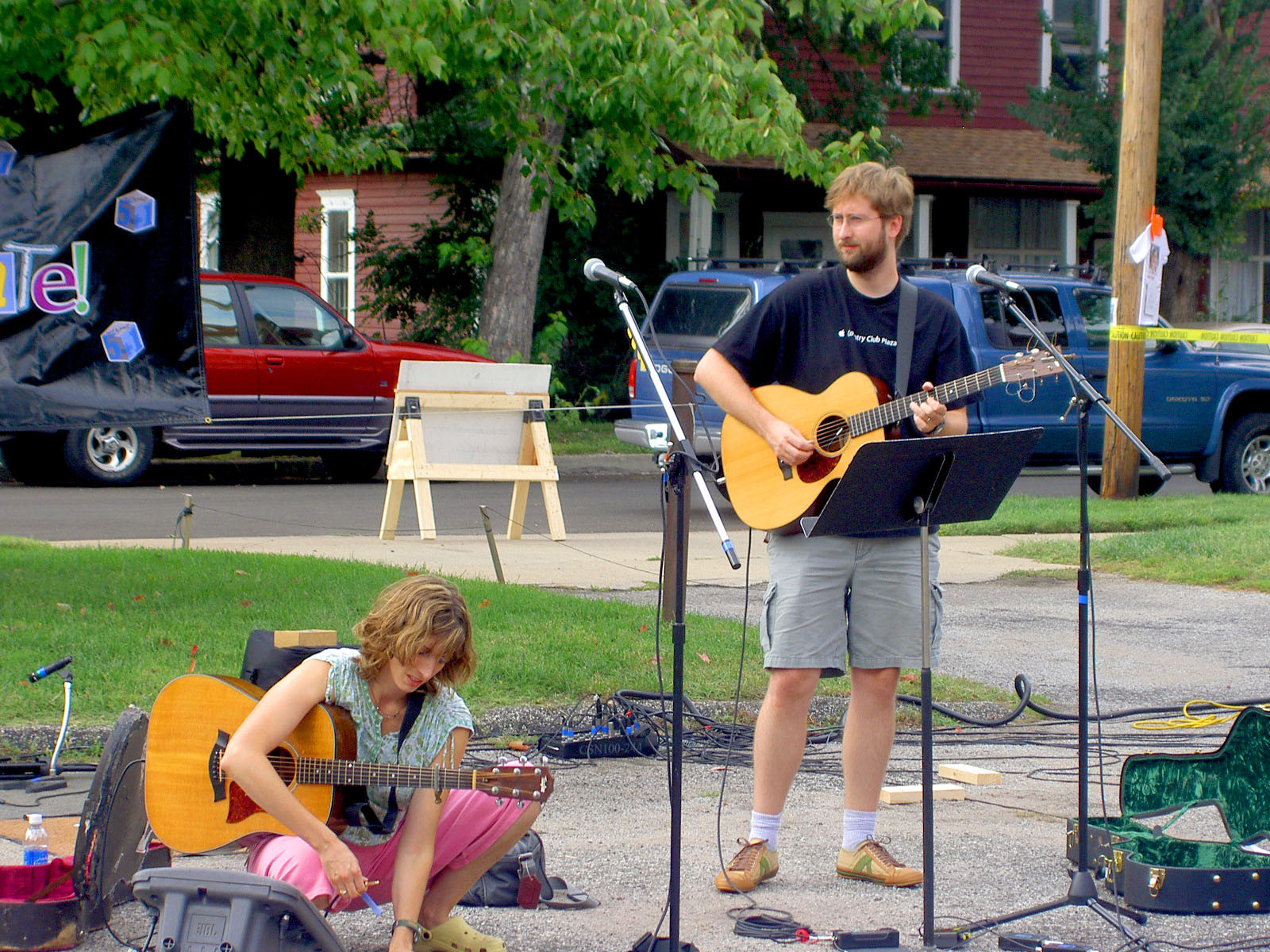Don and Lori Chaffer, holding guitars outside on a sidewalk