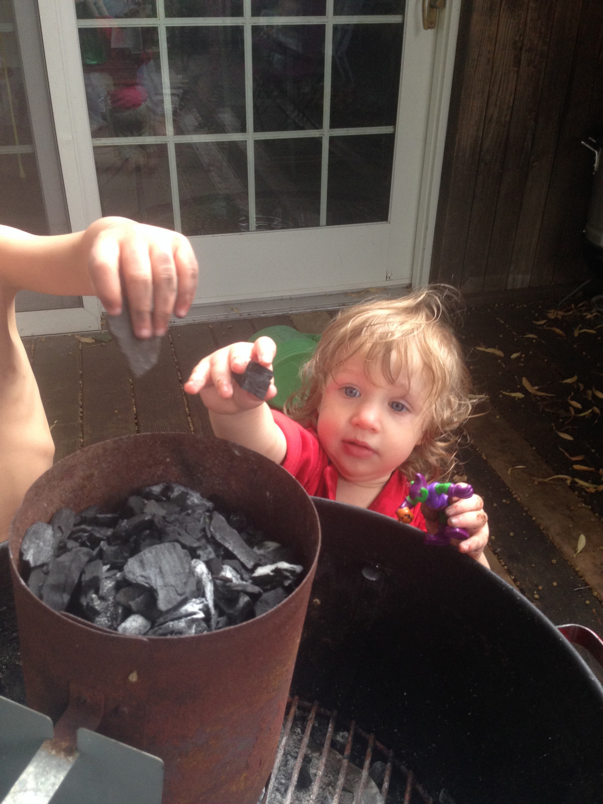 A little girl and a little boy putting charcoal pieces in a chimney starter