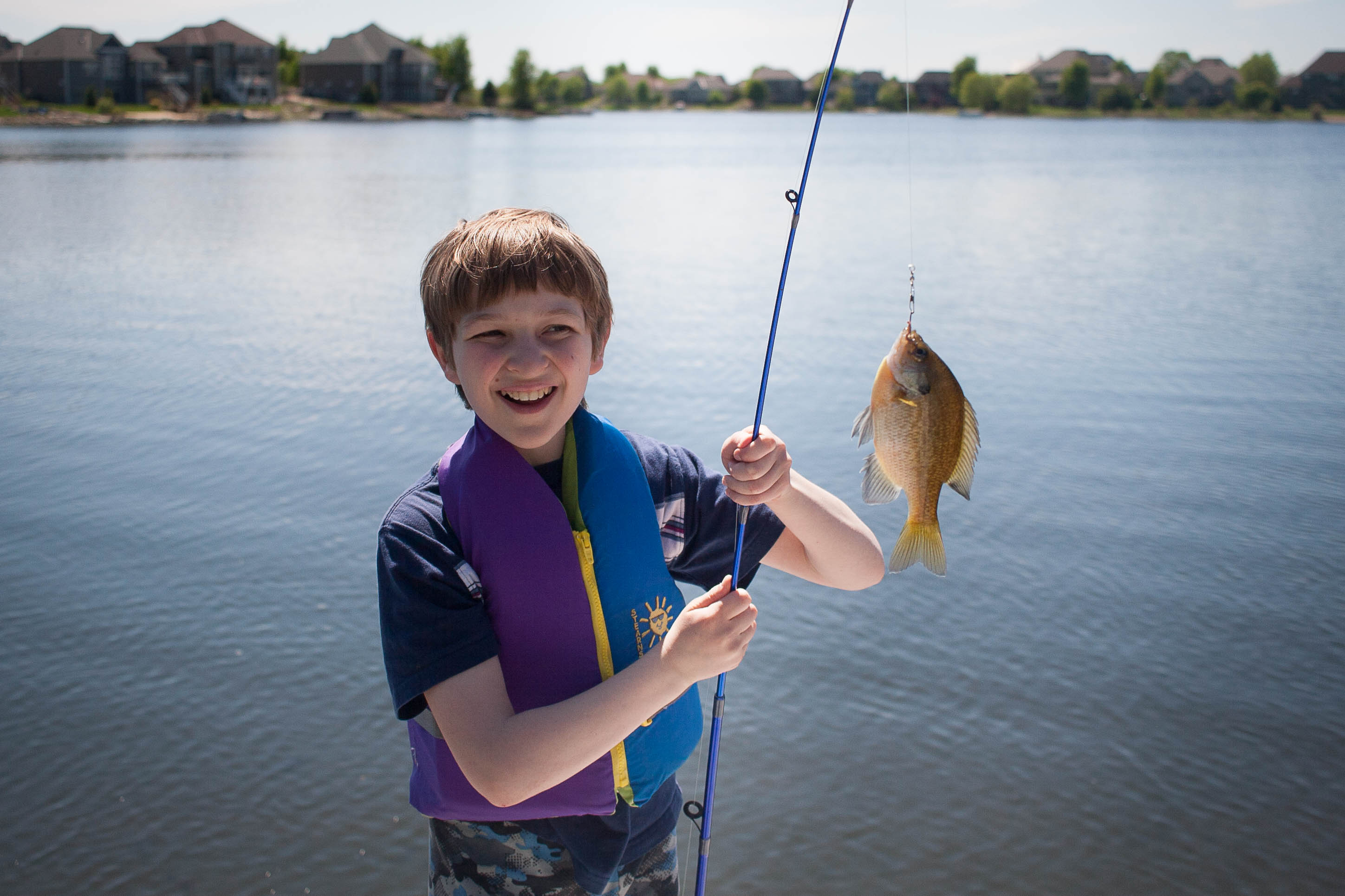 A boy wearing a life jacket smiling at a fish he just caught